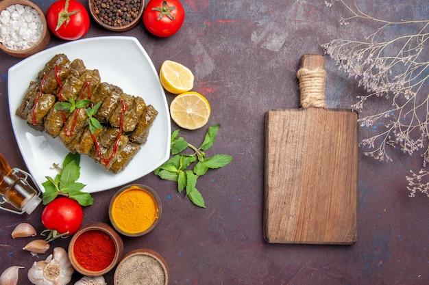 Vista dall'alto deliziosa foglia dolma con condimenti e pomodori sullo sfondo scuro piatto a base di carne cibo cena