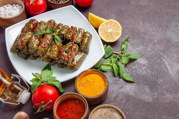 Vista dall'alto deliziosa foglia dolma con condimenti e pomodori su sfondo scuro piatto di carne cena alimentare a base di foglie