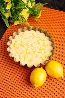 A top view delicious lemon cake sour delicious exotic bakery cake sweet on the dark desk