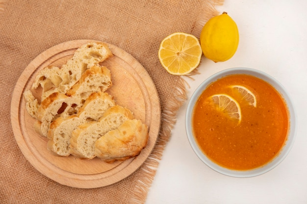 Top view of delicious lentil soup on a bowl with bread slices on a wooden kitchen board on a sack cloth with lemons on a white surface