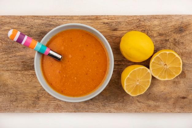 Vista dall'alto di una deliziosa zuppa di lenticchie su una ciotola su una tavola di cucina in legno con cucchiaio con limoni su sfondo bianco