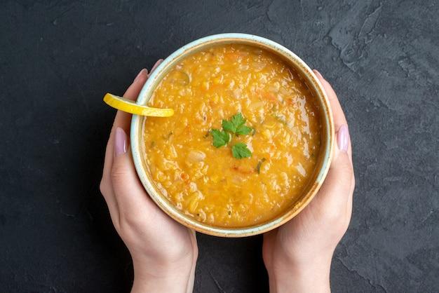 어두운 표면에 여성 지주 접시 어두운 빵 덩어리와 상위 뷰 맛있는 렌즈 콩 수프