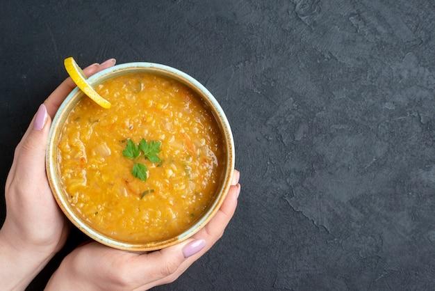 暗い表面に女性の保持プレートを備えた上面図おいしいレンズ豆のスープ
