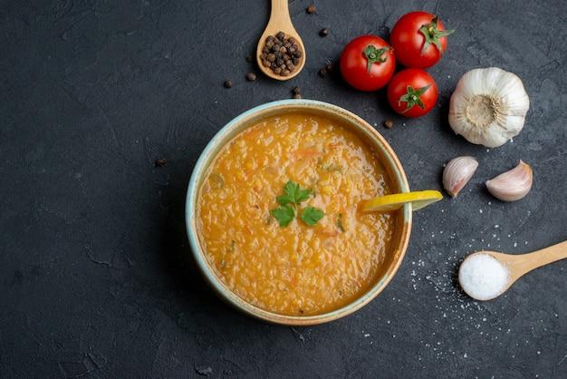 Vista dall'alto deliziosa zuppa di lenticchie con aglio e pomodori sulla superficie scura