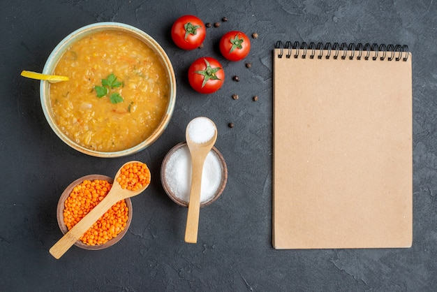 暗い表面に塩と赤いトマトが入ったトップビューのおいしいレンズ豆のスープ