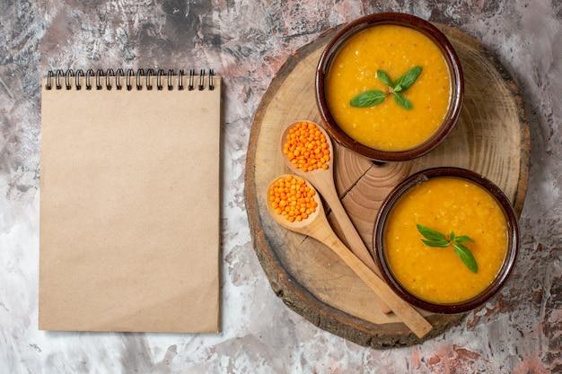 平面図明るい背景のプレート内のおいしいレンズ豆のスープ種子植物のスープ色食品皿の写真