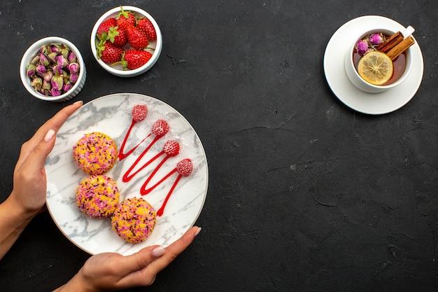 Vista dall'alto deliziosi piccoli biscotti con una tazza di tè sullo spazio grigio