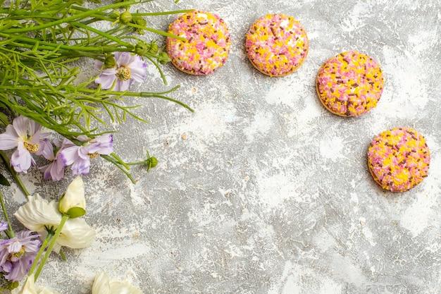 흰색 표면 쿠키 달콤한 비스킷에 꽃과 상위 뷰 맛있는 작은 비스킷