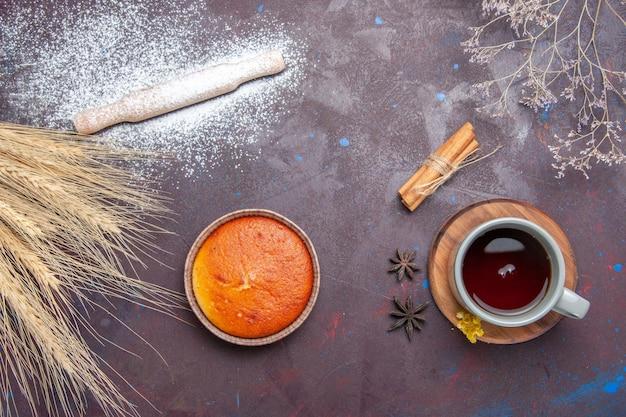 Vista dall'alto deliziosa piccola torta dolci perfetti per una tazza di tè su sfondo scuro torta dolce torta torta zucchero pasta biscotto