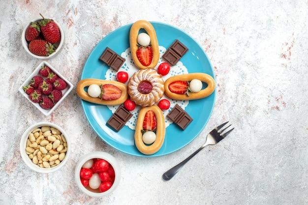 トップビューチョコレートバーと白い背景の上の甘いクラッカーとおいしい小さなケーキクラッカー甘いビスケットケーキパイティー