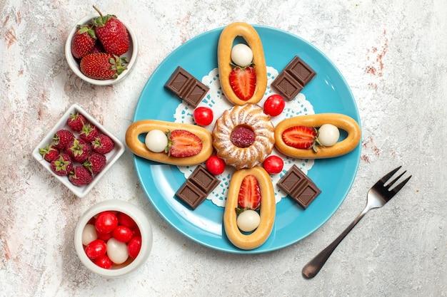 トップビュー白い背景のクラッカー甘いビスケットケーキパイティーにチョコレートバーと甘いクラッカーとおいしい小さなケーキ