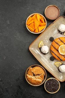 トップビューダークグレーのデスクティーケーキビスケットクッキーデザートにココナッツキャンディーとおいしい小さなケーキ