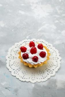 Вид сверху вкусный маленький торт со сливками и красными фруктами на серой поверхности сладких фруктов