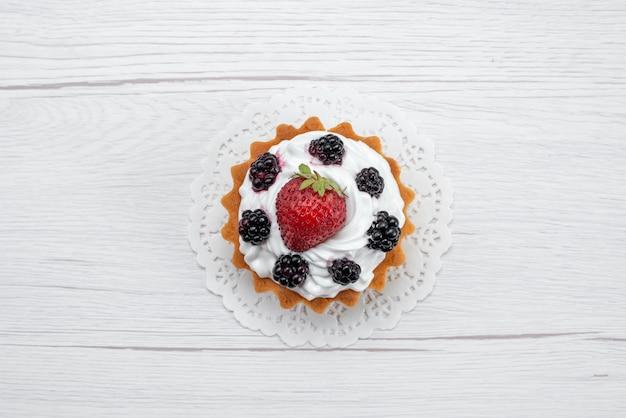 Vista dall'alto di una deliziosa piccola torta con crema e frutti di bosco su bianco, torta biscotto cuocere frutta dolce