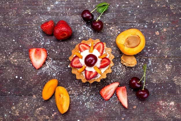 A top view delicious little cake with cream and fresh sliced fruits on the brown desk fruit cake biscuit