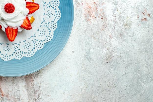 Vista dall'alto deliziosa piccola torta con panna e fragole sulla scrivania bianca