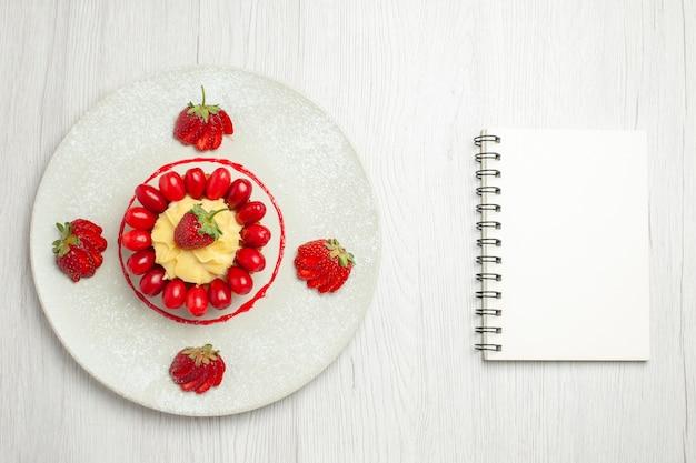 Vista dall'alto deliziosa piccola torta con frutta all'interno del piatto sulla scrivania bianca
