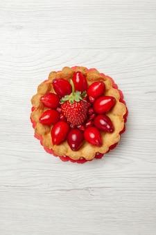 白い机の上にフルーツとトップビューのおいしい小さなケーキ