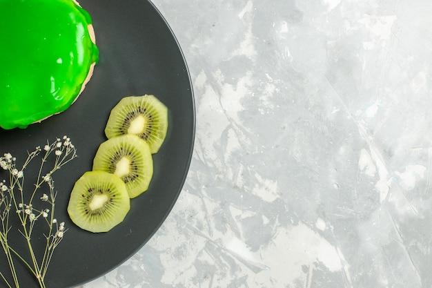 上面図白い背景の上のプレートの内側に緑のアイシングとおいしい小さなケーキビスシウト甘い砂糖パイ