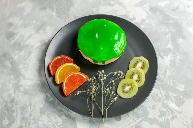 Вид сверху вкусный маленький торт с зеленой глазурью внутри тарелки на белой поверхности торт бисквитный сладкий сахарный пирог