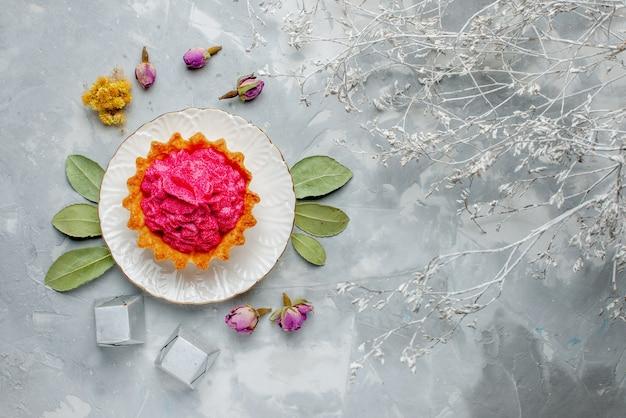 Vista dall'alto di deliziosa piccola torta con crema rosa e cioccolatini su luce, torta dolce crema tè cuocere