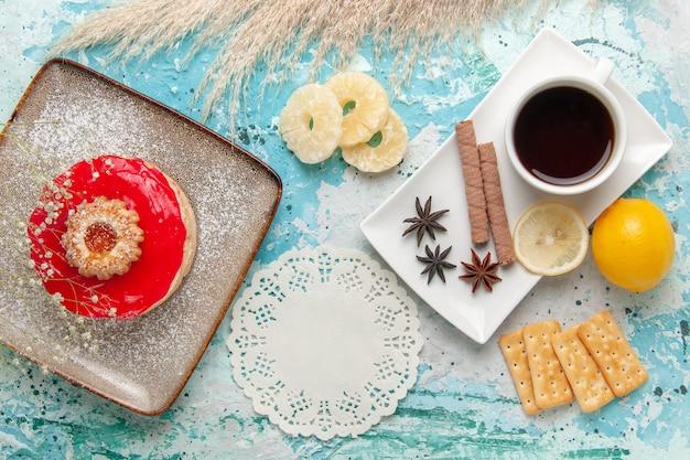 上面図赤いクリームクラッカーと青い背景のお茶とおいしい小さなケーキクッキー甘いビスケットシュガーパイケーキティー