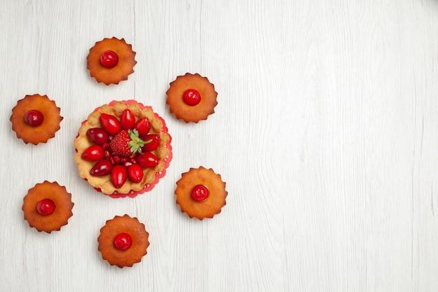 Вид сверху вкусные маленькие пирожные на белом столе