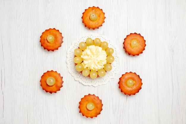 トップビューおいしい小さなケーキ白いデスクケーキパイ甘いデザートティーに並ぶお茶にぴったりのスイーツ