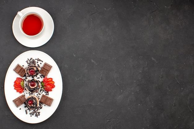 トップビュー暗い背景にチョコレートとお茶のおいしい小さなケーキココアケーキパイ甘いお茶