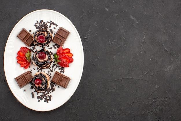 トップビュー暗い背景にチョコレートバーとイチゴのおいしい小さなケーキココアケーキパイ甘いお茶