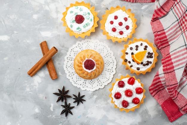 Вид сверху вкусные маленькие пирожные со сливками и красными фруктами с корицей на светлом столе фруктовая сладость