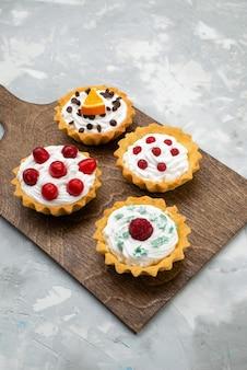 トップビューの軽い表面の甘いフルーツのクリームと赤いフルーツのおいしい小さなケーキ