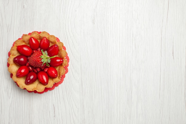 Вид сверху вкусные маленькие пирожные с фруктами на светло-белом столе