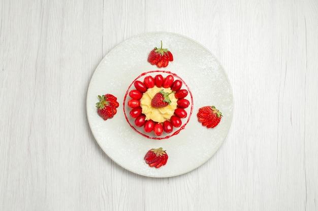 ライトホワイトの机の上にフルーツとおいしい小さなケーキの上面図