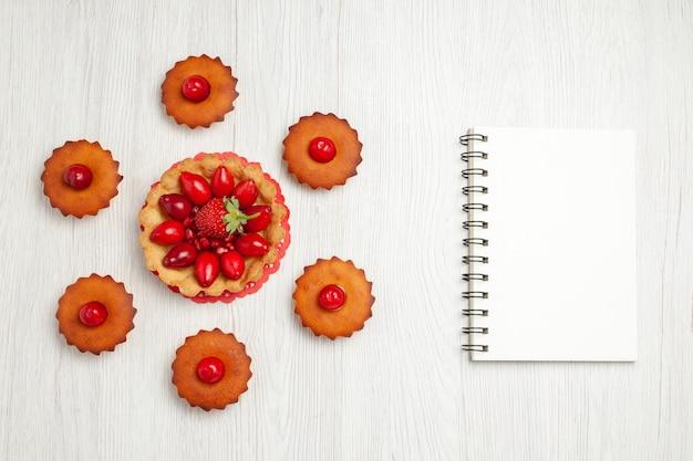 Vista dall'alto deliziose torte con frutta sulla scrivania bianca