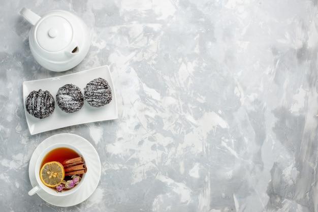 Вид сверху вкусные маленькие пирожные с глазурью и чашкой чая на светло-белом фоне чайный бисквитный торт испечь сахарный сладкий пирог