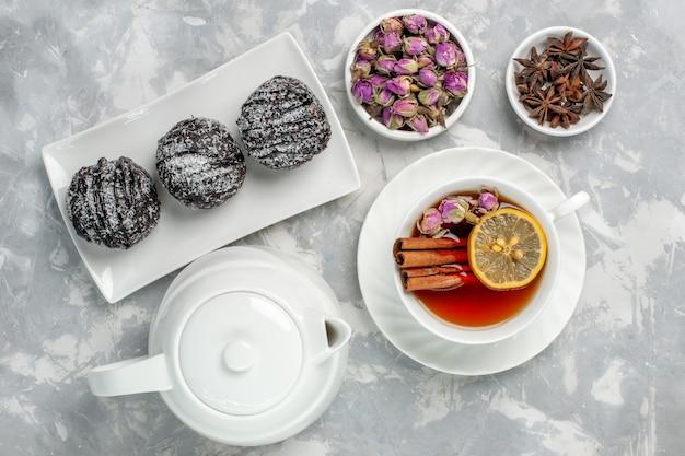 Вид сверху вкусные маленькие пирожные с глазурью и чашкой чая на светло-белой поверхности чайный бисквитный торт испечь сахарный сладкий пирог печенье
