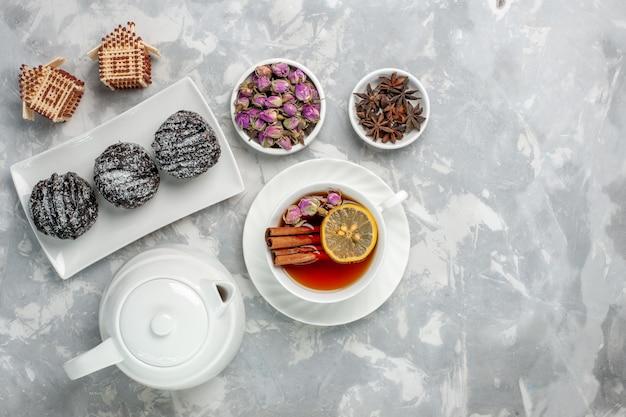 トップビュー白い机の上にアイシングとお茶を入れたおいしい小さなケーキティービスケットケーキ焼き砂糖甘いパイ