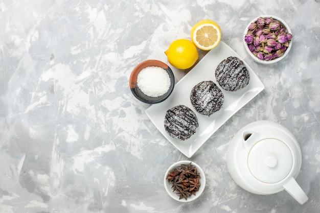 上面図白い背景にレモンとおいしい小さなケーキチョコレートココアケーキビスケット甘い砂糖茶