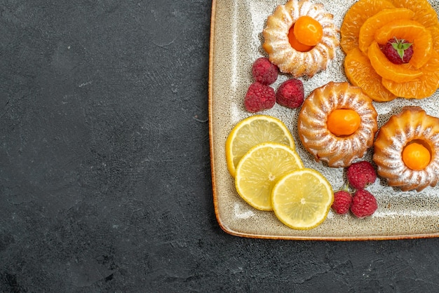 Top view delicious little cakes with lemon slices and tangerines on the dark background fruit biscuit sweet tea cookie