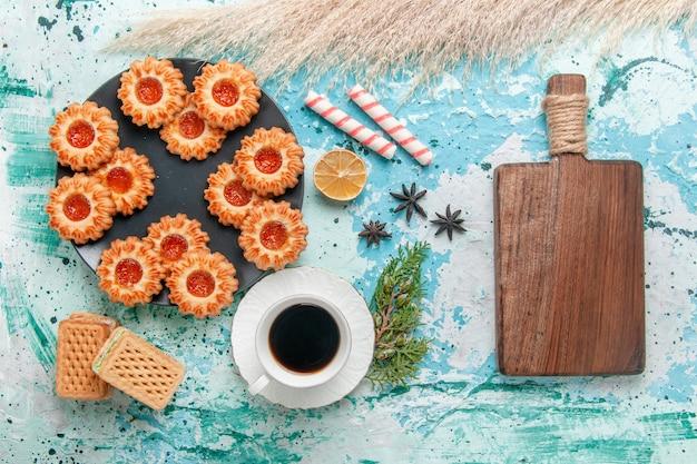 Vista dall'alto deliziosi piccoli biscotti con una tazza di caffè e cialde sulla scrivania blu biscotto biscotto dolce zucchero colore tè