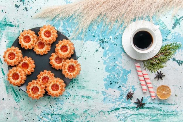 上面図青い机の上のコーヒーのカップとおいしい小さなクッキークッキービスケット甘い砂糖色のお茶