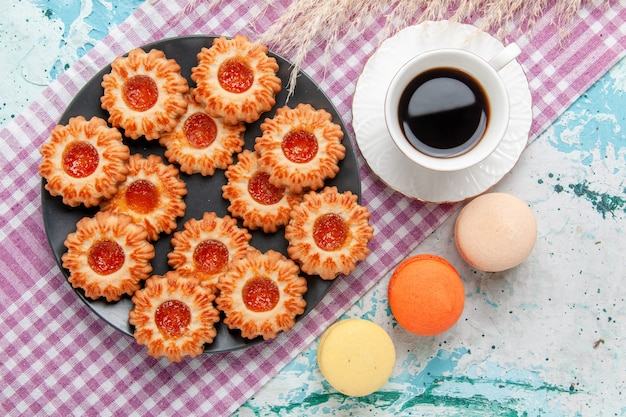 Вид сверху вкусного маленького печенья с французскими макаронами и кофе на синем столе печенье печенье сладкий чай цвета сахара