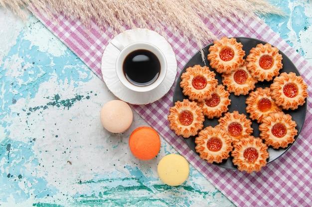 トップビューおいしい小さなクッキーとフレンチマカロンと青い机の上のコーヒークッキービスケット甘い砂糖色のお茶