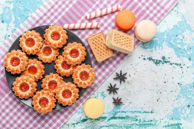 上面図オレンジジャムマカロンと青い机の上のワッフルとおいしい小さなクッキークッキービスケット甘い砂糖色のお茶