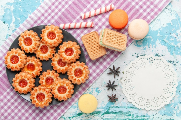 Vista dall'alto deliziosi piccoli biscotti con marmellata d'arancia macarons e cialde sulla scrivania blu biscotto biscotto dolce zucchero colore tè