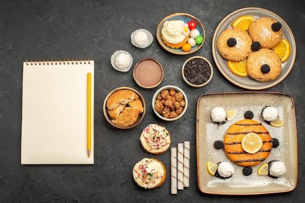 トップビューダークグレーの表面にクッキーとケーキが入ったおいしい小さなパイケーキティービスケットクッキースウィート