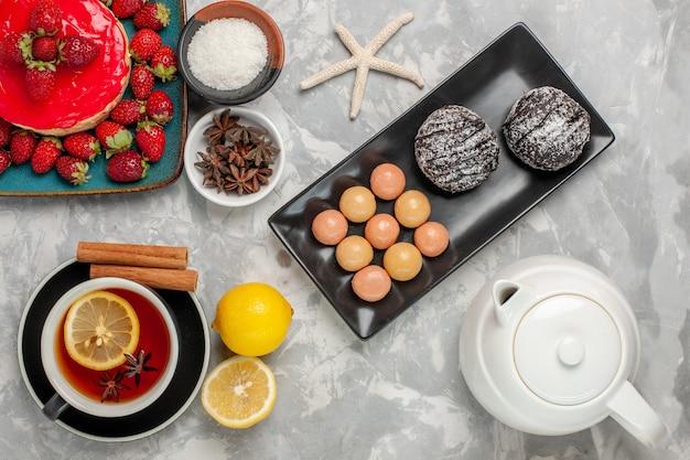 Torta dall'aspetto delizioso vista dall'alto, piccola torta con una tazza di biscotti da tè e fragole fresche su una superficie di colore bianco chiaro, torta di biscotti, crema dolce