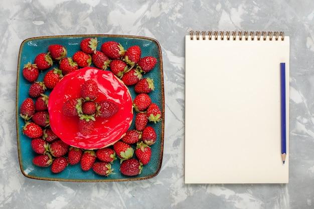 Вид сверху вкусный торт маленький пирог с красным кремом и свежей клубникой на белом фоне торт бисквит выпечка крем сахар сладкое печенье