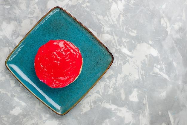 Вид сверху восхитительно выглядящий торт маленький пирог с красным кремом на светлом белом фоне торт бисквит выпечка крем сахар сладкий